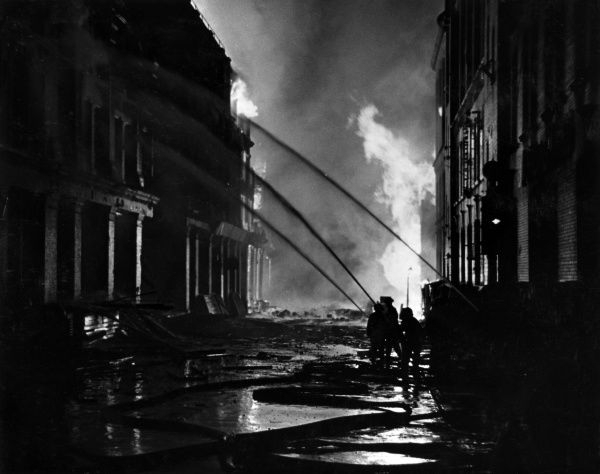 Blitz in the City of London - AFS firefighters at work with hoses following a bombing raid