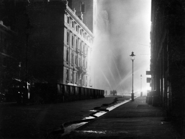 London firemen at work with hoses in Queen Victoria Street following a bombing raid and incendiary attack, 10-11 May 1941
