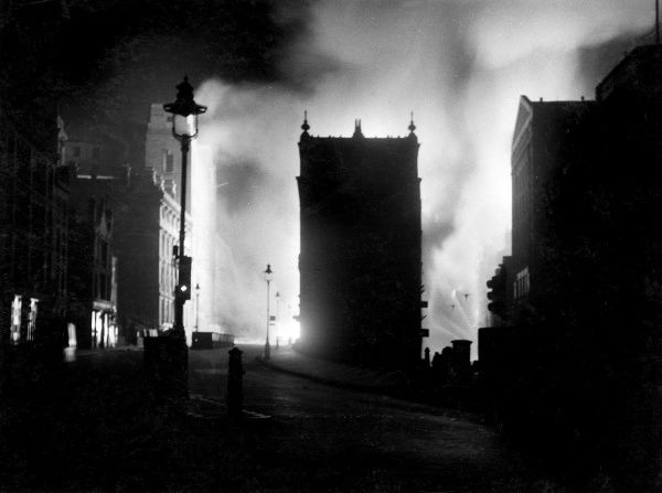 Scene in Queen Victoria Street and Upper Thames Street following a bombing raid and incendiary attack, 10-11 May 1941, with firemen at work in the distance