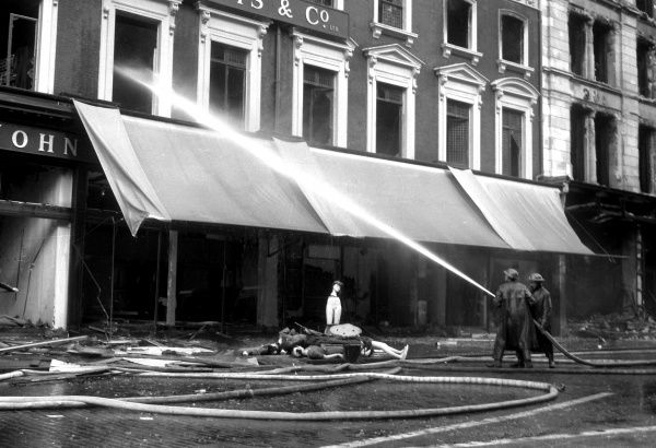 Fire crews, using jets of water, continue to extinguish the fires in London's main shopping district, Oxford Street, W1, after high explosive and incendiary bombs caused widespread damage and started very many serious fires on 18 September 1940