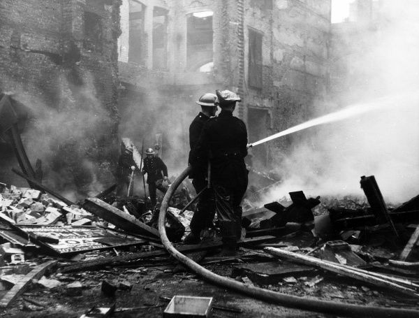 Blitz in London -- the site of Wolfe & Hollander Ltd, bombed on 8 December 1940, with firefighters in action with hosepipes