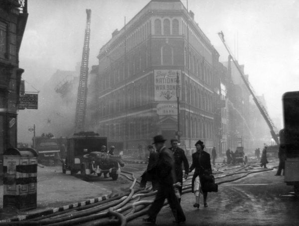 Blitz in London -- St Bride Street and Farringdon Street, with firefighters at work in a smoky atmosphere and pedestrians walking by. On the corner is the British Mutual Bank where National War Bonds may be bought to help the war effort