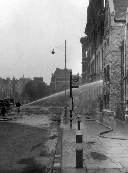 Blitz in London -- firefighters in action with hoses at John Oakey & Sons, Westminster Bridge Road. The building is at risk, as the wall is bulging