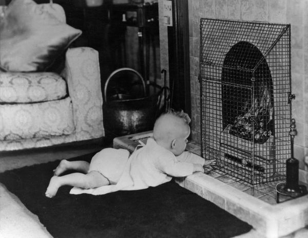 Fire safety -- a baby playing near a guarded coal fire