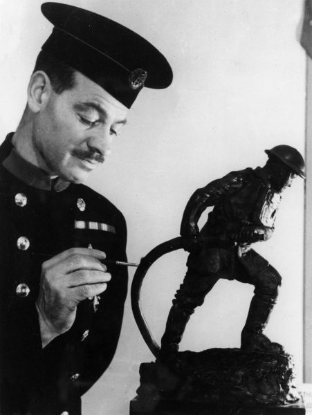 Fireman painting a statuette of a firefighter in action