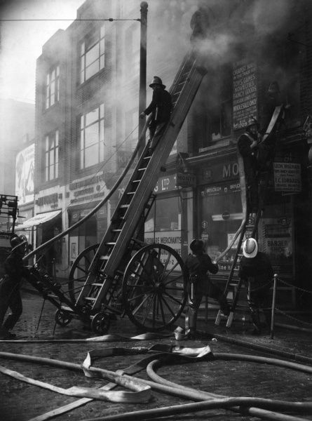 Firefighters in action with hosepipes at business premises, 81/85 Commercial Road, East London, 18 June 1957