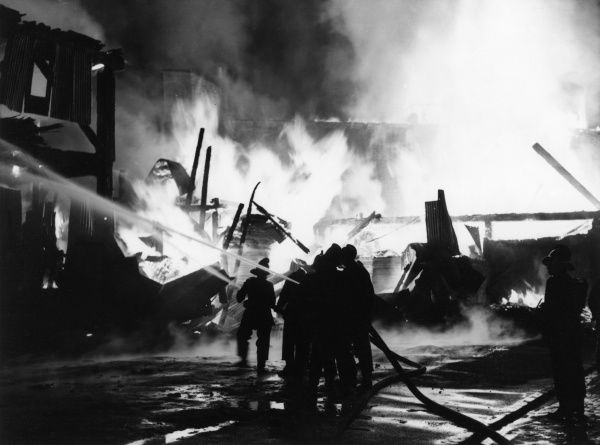 Firefighters in action with hosepipes at a blazing fire, London