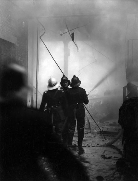 Firefighters in action with hosepipes during a fire at a warehouse in Victory Place, Southwark, SE17, on 27 April 1958