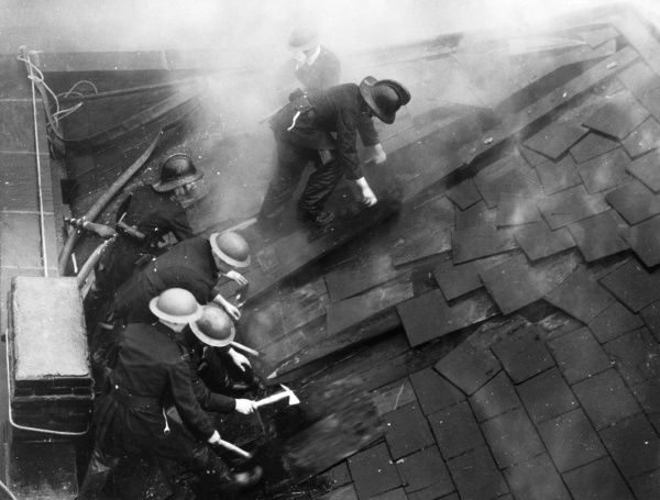 Firefighters cutting through the roof of a burning building