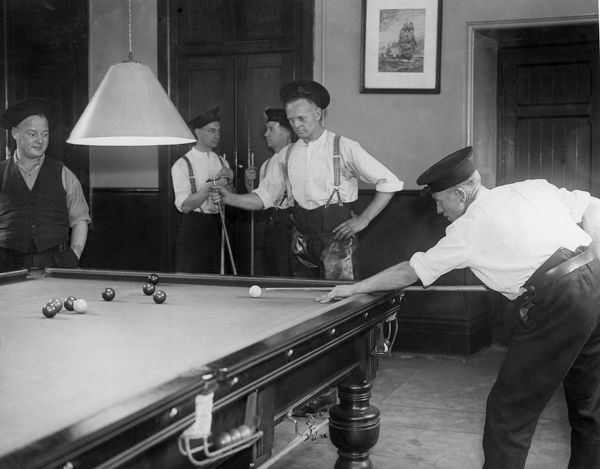 Firemen playing billiards in a fire station