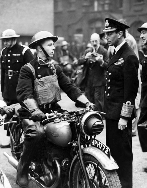 King George VI visiting the Headquarters of the London Fire Brigade in Lambeth on 16 October 1940 during the Second World War. Seen here speaking with a despatch riders on his motorbike