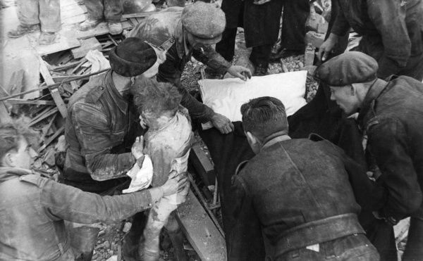 Scene in Sherard Road, Eltham, London SE9, during the Second World War, showing the aftermath of an air raid, 18 November 1944. Rescue workers extract a boy from the rubble of his ruined home. He was one of two survivors of a family of four