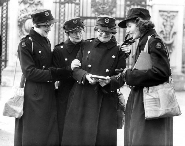 Section Officer M. Pennington of Southwark Fire Station showing her OBE medal to AFS colleagues, Second World War (5 March 1941)