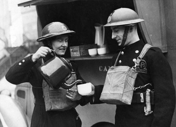 Tea break for a man and woman of the AFS (Auxiliary Fire Service), standing by a canteen van in London, Second World War