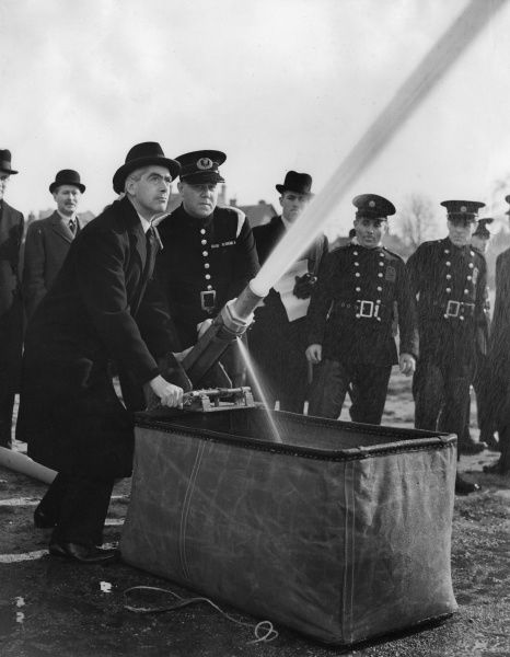 William Shepherd Morrison (later 1st Viscount Dunrossil, 1893-1961), Postmaster General and Chairman of the Fire Prevention Executive, taking part in a firefighting demonstration on Wimbledon Common on 4 March 1941, with newly appointed chiefs