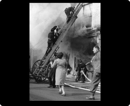 Fire at 298 Old Brompton Road, London SW5, 25 February 1956. An escape ladder is extended to the second floor, with Sub Officer Kirby of A9 Fulham carrying a 19-month-old child, Dennis Norman McGowan, down in his arms, and Sub Officer Temple following
