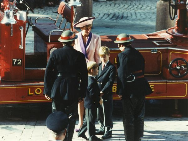 Princess Diana and her sons, Princes William and Harry, meeting firefighters at the The Blitz Remembered Service at St Pauls Cathedral, London, on 25 October 1990. A red fire engine can be seen behind them