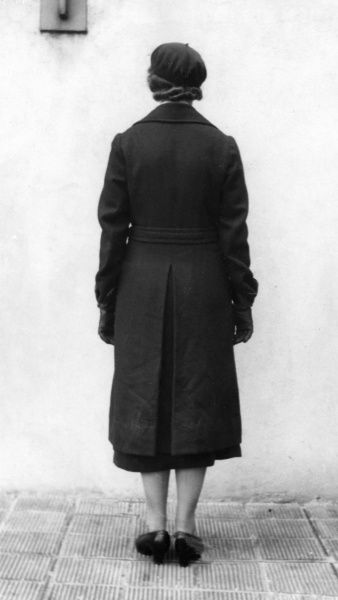 AFS woman in double-breasted greatcoat, beret, white scarf and armband (back view)