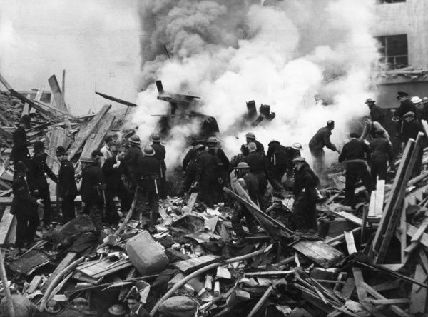 Firefighters, policemen and rescue personnel in the debris of a building during the aftermath of a V2 rocket attack in Middlesex Street, Aldgate, London E1, 10 November 1944