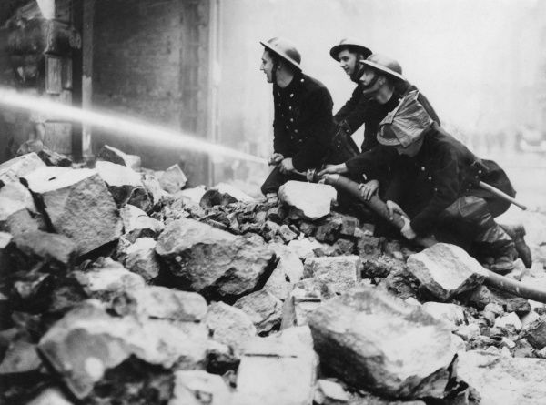 Blitz in the City of London -- a group of firefighters in action in Newgate Street with a hosepipe, perched on a pile of rubble
