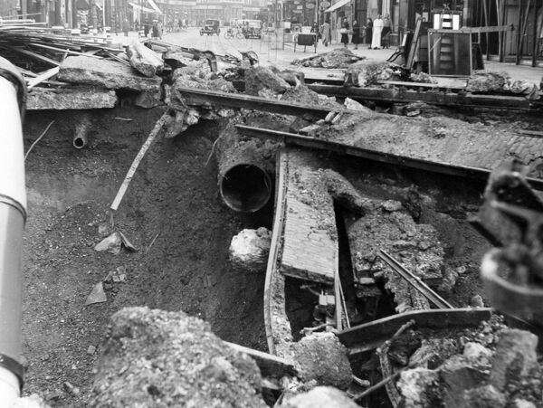 Blitz in London -- a bus in a bomb crater in Balham High Road, SW London, 14 October 1940. Showing a 24-inch broken water main (centre), and a smaller one on the left