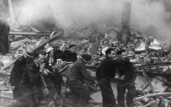 Blitz in London -- a casualty who has just been rescued from the rubble is carried on a stretcher to an ambulance. (3 of 3)