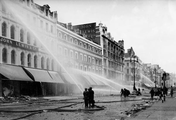 Fire crews, using radial branches, extinguishing fires in London's main shopping district of Oxford Street, W1, after high explosive and incendiary bombs caused widespread damage and started very many serious fires on 18 September 1940