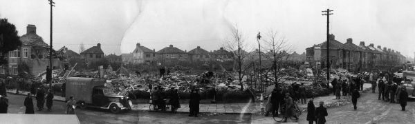 Panoramic view of extensive bomb damage in Brampton Road, Bexleyheath, Kent, 14 November 1944, with ambulances ready to remove casualties from the scene