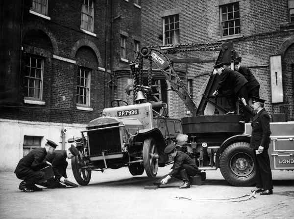 Firefighters operating a Dennis breakdown lorry (commissioned at HQ on 3 April 1936), demonstrating the wrong method of lifting and towing the front axle