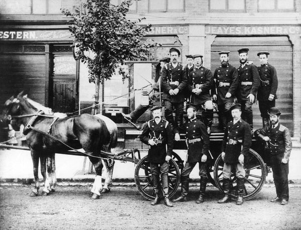 Firefighters of the Ealing Fire Brigade, West London, with a horse-drawn appliance