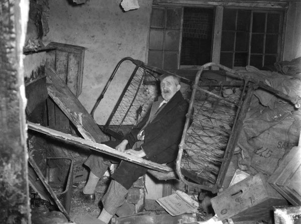 Fire at Langley Court, London WC2, 2 February 1956. Showing an elderly man occupying a derelict room on the top floor, with timber planks used in an open fireplace for heating