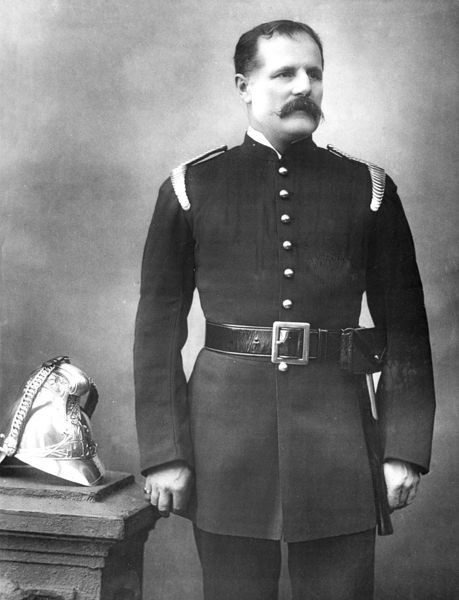 A fire officer (James Seaton Simonds?) in a studio photograph. He is wearing uniform, and his brass helmet is at his side