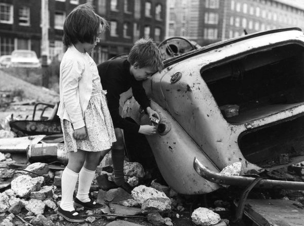 Fire safety for children -- a boy and girl playing near a wrecked car. The boy is about to strike a match near the open fuel cap. If the car still contains petrol there could be an explosion and the children could be badly injured