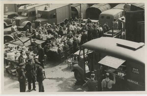 Fire station staff having a meal supplied from a mobile canteen van in a school playground in London during the Second World War
