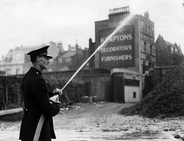 Firefighter operating a two-man manual hose in Orange Street, London W1, 21 September 1942