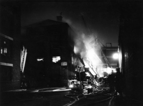 Firefighters in action with hosepipes at night, at a fire in Shad Thames, 19 February 1958, at the premises of Corry & Co, showing the Gainsford Street/Maguire Street corner of the building. At this stage the first floor was completely involved