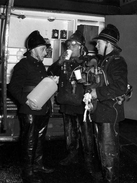 LFB firefighters in breathing apparatus, taking salt tablets for rehydration after attending a fire