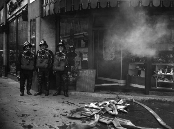 LFB firefighters in breathing apparatus outside the main entrance to the Chinacraft store, 499 Oxford Street, London, on 28 July 1958. A fire had occurred in the basement area