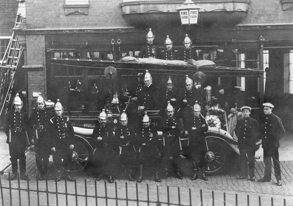 Firefighters and fire engine posing outside a fire station