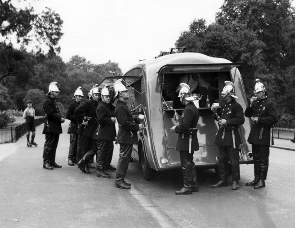 Firefighters in traditional brass helmets enjoying some refreshments outside a canteen van in Battersea Park, London, watched by a boy on roller skates