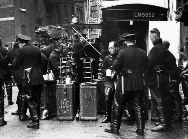 Firefighters on a refreshment break next to a canteen van at Wapping, East London, during a serious fire on 25 September 1935