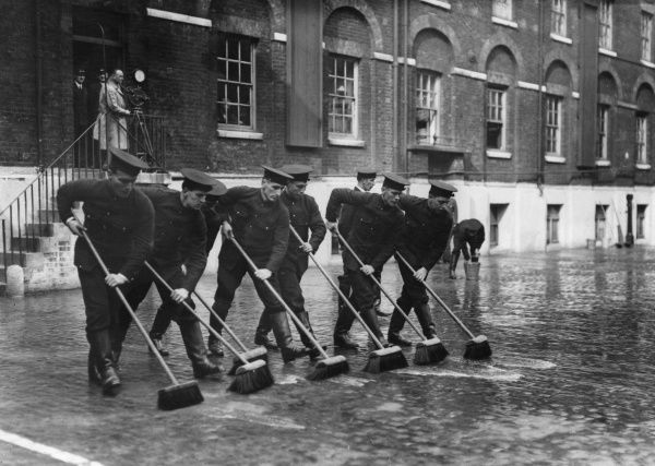 Firefighters with sweeping brushes at Southwark HQ, taking part in an escape competition