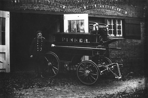 George Beaumont, Chief Officer of the Pinner Voluntary Fire Brigade, with a manual fire engine which was kept at Waxwell Lane, Pinner, having previously been housed at The Hall, and later at The George