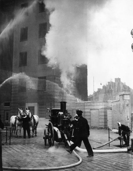 A horse-drawn steamer and crew taking part in a special drill display given at Lambeth HQ for chief officers of provincial fire brigades on 13 October 1937. Seen here are hosepipes in action