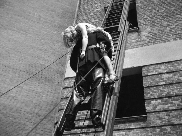 LFB escape training at HQ, 17 July 1955. A firefighter carries a woman down a ladder