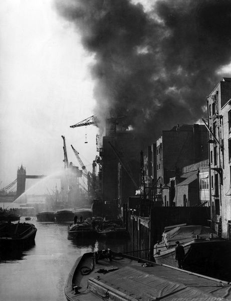 A fireboat tackles a fire at Colonial Wharf. A typical big Thameside fire of the sort which the London fire Brigade had tackled over 100 years: Colonial Wharf, Wapping High Street, E1, 27th September 1935. This nine-storey warehouse was full of crude rubber