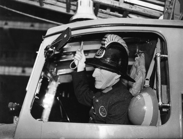 LFB firefighter at the window of a new enclosed pump vehicle with a ladder on top, about to ring the bell