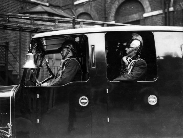 LFB firefighters in an enclosed pump vehicle with a ladder on top. They are wearing traditional brass helmets and breathing equipment