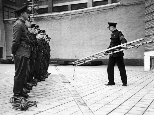 LFB recruits taking part in hook ladder training at HQ -- the squad instructor, O Kitching, demonstrates how to pick up a hook ladder