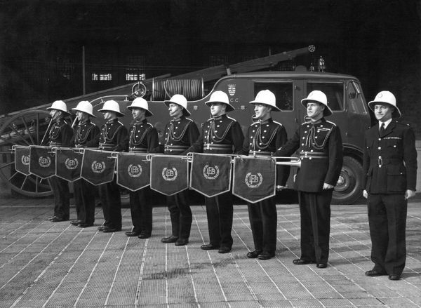 Members of the LCC-London Fire Brigade band, standing in a row with their fanfare trumpets. The pith helmets seen here were later replaced with brass helmets